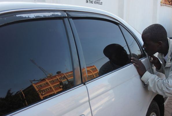 thief looking inside car with tinted windows